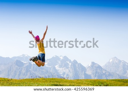 traveling girl jumping in the mountains  - stock photo