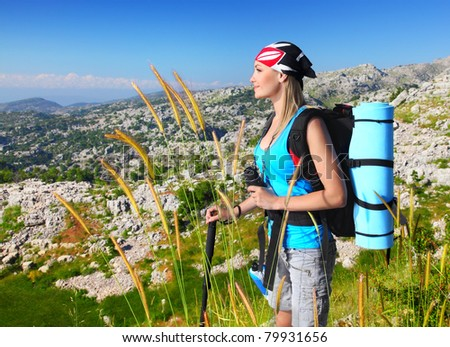 Traveling girl with backpack hiking in the mountains, eco tourism, freedom concept - stock photo