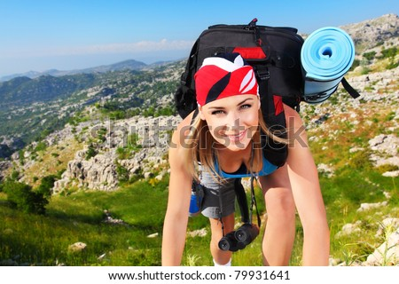 Traveling girl with backpack hiking in the mountains, freedom concept - stock photo