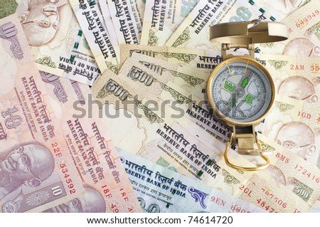 traveling india with compass and  indian currency rupee - stock photo