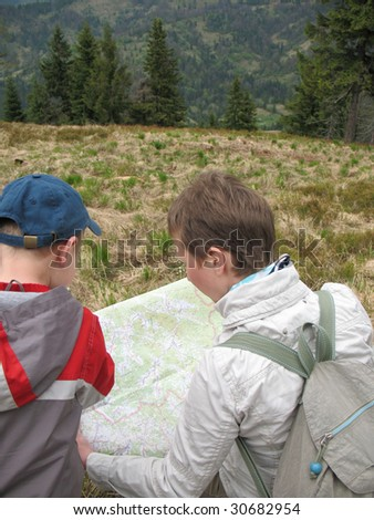 traveling people reading map on mountains - stock photo
