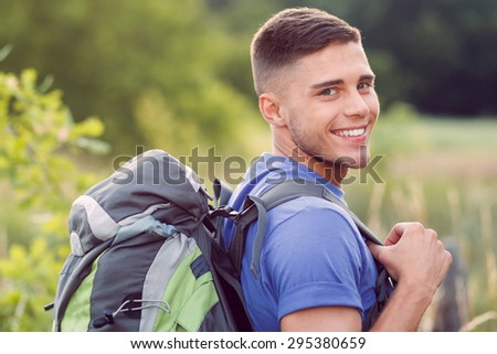 Traveling. Portrait of a young handsome tourist wearing blue t-short and backpack standing in a profile looking at the camera smiling - stock photo