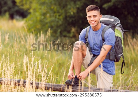 Traveling. Portrait of a young handsome tourist wearing blue t-short and backpack standing leaning his foot on the fence tying shoelaces on his sneaker  - stock photo