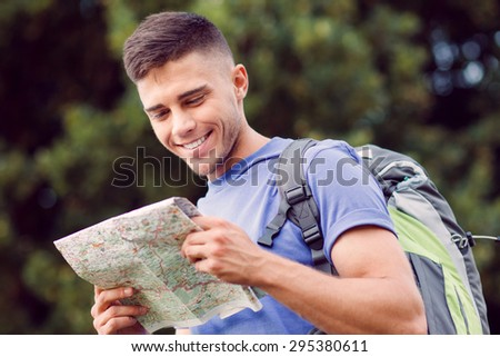 Traveling. Portrait of a young handsome tourist wearing blue t-short and backpack standing smiling and looking at the map in his hands - stock photo