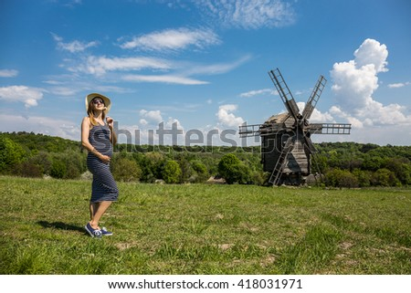 Traveling & Pregnancy concept: pregnant woman near authentic windmill in Eastern Europe