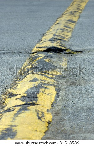 Traveling the length of a yellow speed bump, which has not been properly maintained. - stock photo