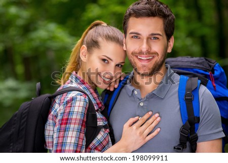 Traveling together is fun. Beautiful young loving couple with backpacks looking at camera and smiling while standing in nature - stock photo