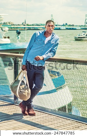 Traveling. Wearing long sleeve shirt, blue pants, brown boot shoes, a hand carrying a duffel bag, a young black college student is standing on dock by the river, beginning of a long journey.  - stock photo