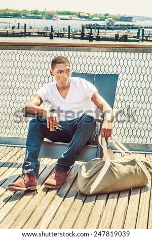 Traveling. Wearing white, V neck T shirt, blue pants, brown boot shoes, a hand carrying duffel bag, a young black college student is sitting on dock by the river, relaxing, thinking, lost in thought. - stock photo