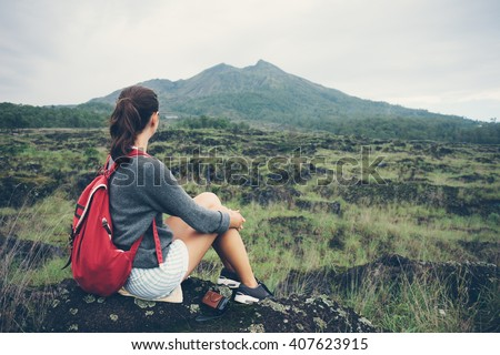 Traveling woman sitting near mountain and looking far away (intentional pale color style) - stock photo