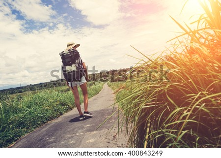 Traveling woman with backpack and hat walking along the road at sunny day (intentional sun glare) - stock photo