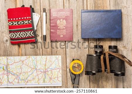 traveller equipment, items include binocullars, compass, pen, passport, map, notebook money - stock photo
