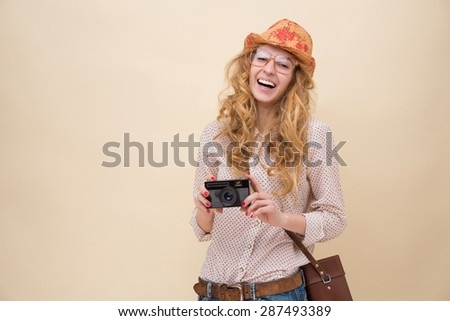 Traveller with long curly red hair making photos of city's sightseeings. Girl in white shirt, with hat on and brown shoulder bag laughing so much.  - stock photo