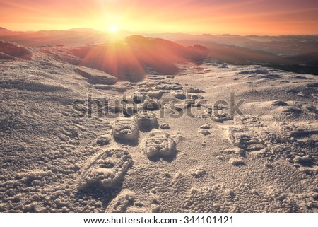 Travellers ascenders leave traces of skis and snowshoes on the slopes of steep mountains in the Alps. Quality equipment is very helpful in extreme climbers hikers traveling in the winter expeditions - stock photo