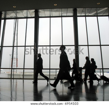 Travellers at an airport, walking to next gate - stock photo