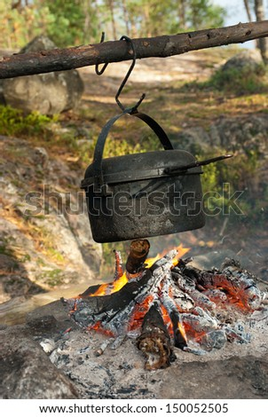 Travelling cooking - kettle over camping fire - stock photo