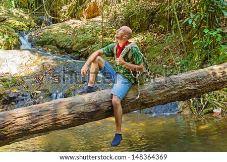 Travelling man sitting on a log near the river in the jungle