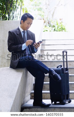 Travelling young businessman using tablet phone outdoor