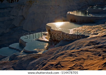 Travertine covered hills and rock pools of Pamukkale Turkey at sunset - stock photo