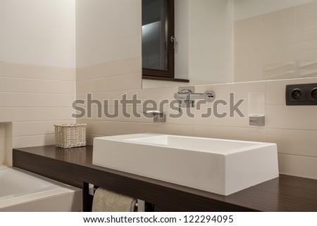 Travertine house - elegant washbasin on wooden shelf - stock photo