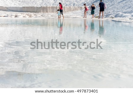 Travertine water surface with unrecognizable people on background, Pamukkale, Denizli, Turkey.