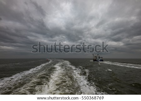 Trawler fishing boat under dramatic sky with tracks