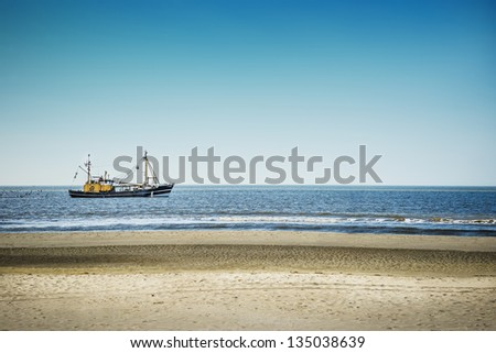 Trawlers in the North Sea on the beach of St. Peter-Ording on a sunny day - stock photo