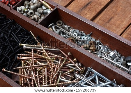 Tray of Construction Hardware. Screws, Nuts, Bolts, Nails, and Washers on a Wood Workbench - stock photo