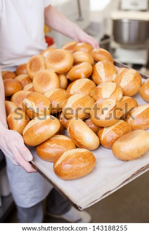 Tray of crisp crusty freshly baked golden rolls on a large tray which has just been removed from the oven by a baker - stock photo