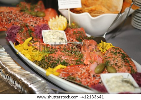 Tray of gourmet smoked salmon with sauce and pickled garnish. - stock photo