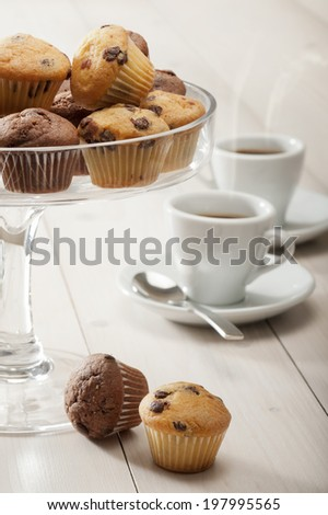 tray of little muffins variety on wooden table whit cups of coffee - stock photo