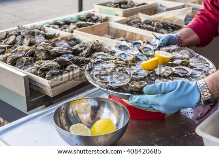 Tray of opened fresh oysters on half shell on ice with lemon in a street of Bordeaux, capital of Aquitaine. France. - stock photo