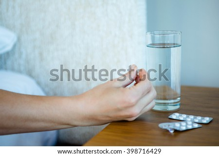 Tray of pills next to a bed with a glass of water