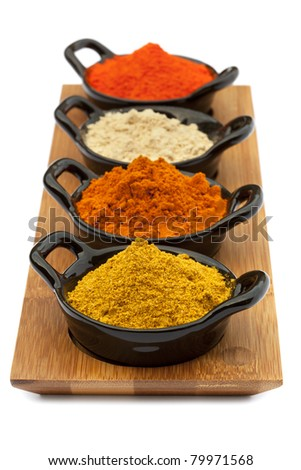 Tray of spices in small black bowls.  Includes Madras curry powder, Malaysian curry powder, ground ginger, and saffron.