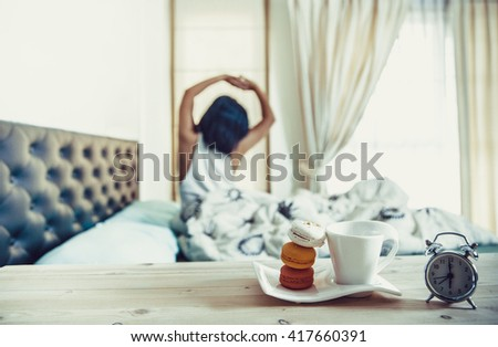 Tray with breakfast  and Young woman stretching in bed Vintage - stock photo