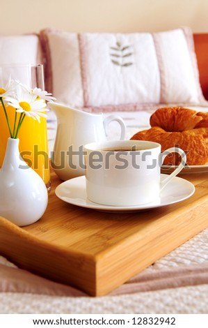 Tray with breakfast on a bed in a hotel room - stock photo