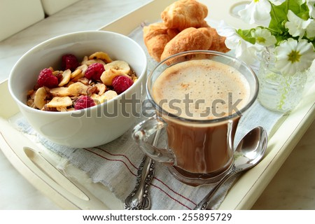 Tray with coffee, cereals with fruits and croissants for breakfast