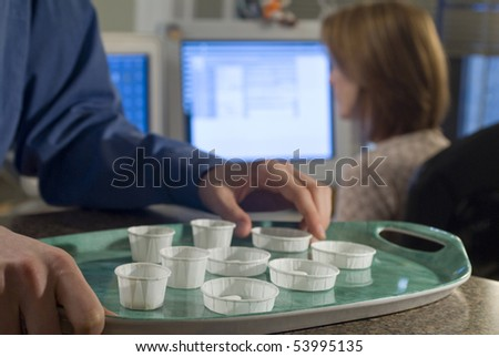 tray with disposable pill cups at nurse station - stock photo