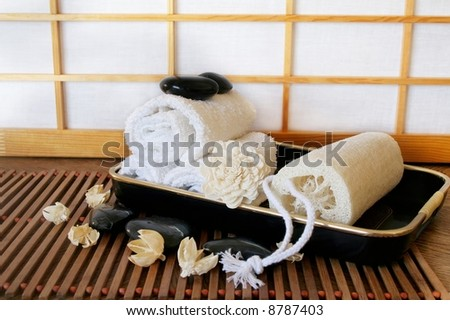 Tray with loofah, towel and scented potpourri on wooden mat with candles and stones; shoji screen background