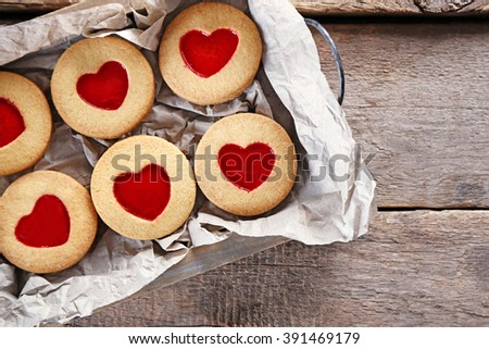 Tray with love cookies on wooden background - stock photo