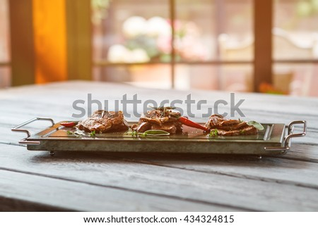 Tray with pieces of meat. Cooked meat and chili pepper. Delicious breakfast served at cafe. Veal medallions with spicy taste. - stock photo