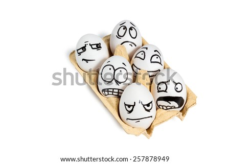 Tray with six eggs with painted faces with different emotions isolated on white background - stock photo