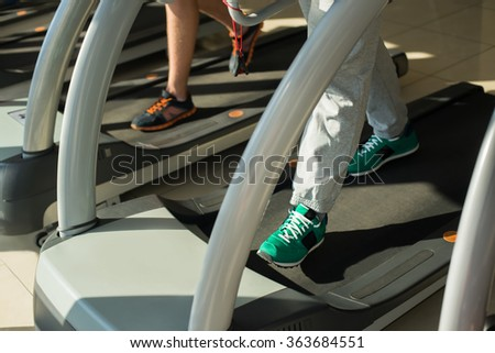 Treadmill in gym. Sportsmen working out in gym. Men running on treadmill. - stock photo