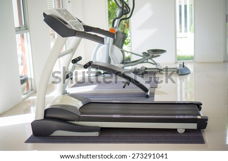 Treadmill trainer in a fitness gym - stock photo