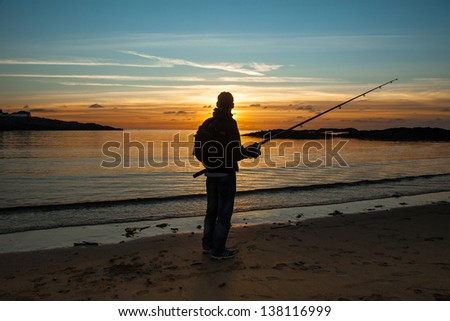 Trearddur Bay and a fisherman in the sunset Isle of Anglesey North wales