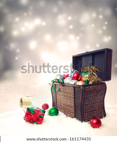 Treasure box filled with Christmas ornaments and presents on snow - stock photo