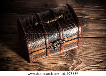 Treasure chest on wooden background - stock photo