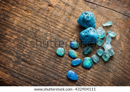 Treasure hunting. Mining for gems. Blue gems on rustic wooden table. Blue Turquoise, blue opals and apatite stones on a wooden table. Shallow depth of field. - stock photo