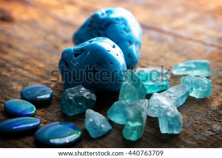 Treasure hunting. Mining for gems. Blue gems on rustic wooden table. Blue Turquoise, blue opals and apatite stones on a wooden table. Focus on large turquoise stone. Shallow depth of field.