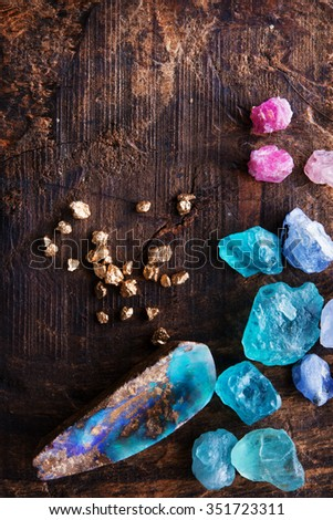 Treasure hunting. Mining for gems. Gold and gem stones on rough wooden surface. - stock photo